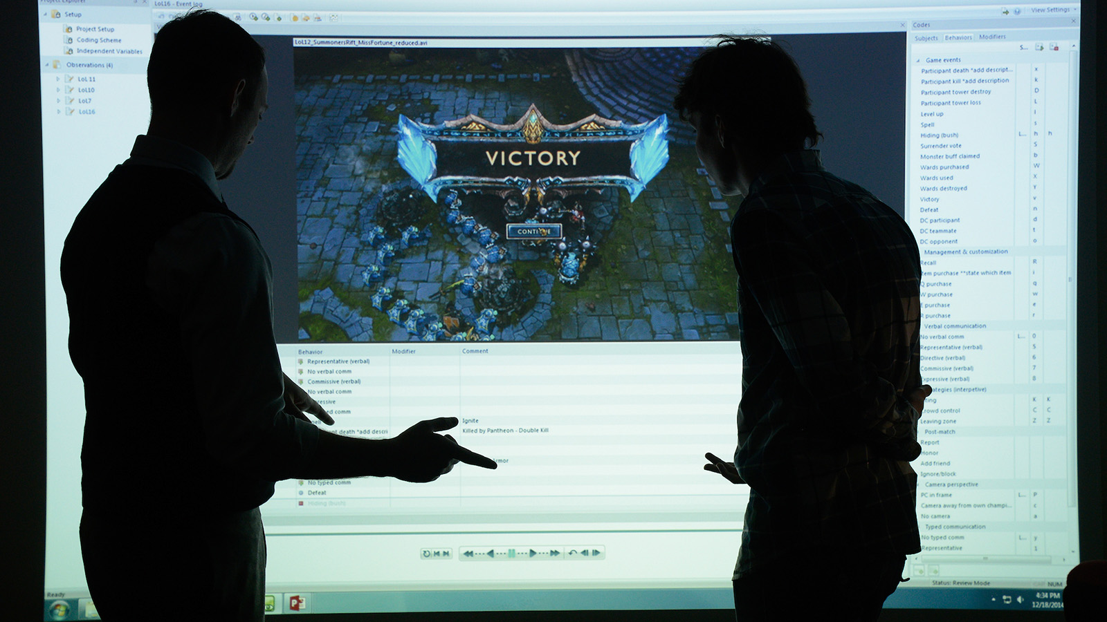 Two people talk while pointing to an over-sized computer screen.