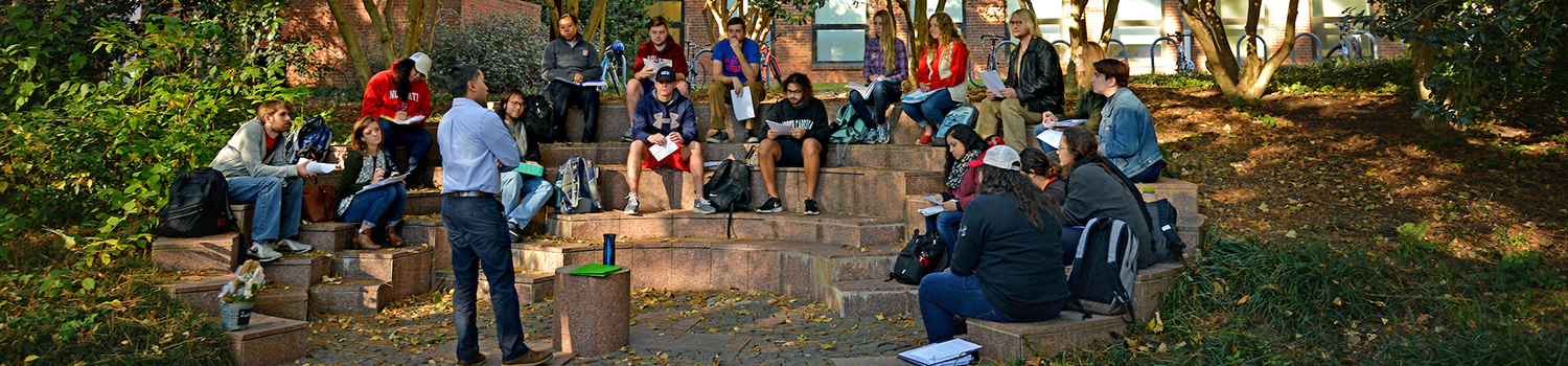 Students sit in a semi-circle, listening to a professor in an outdoor classroom