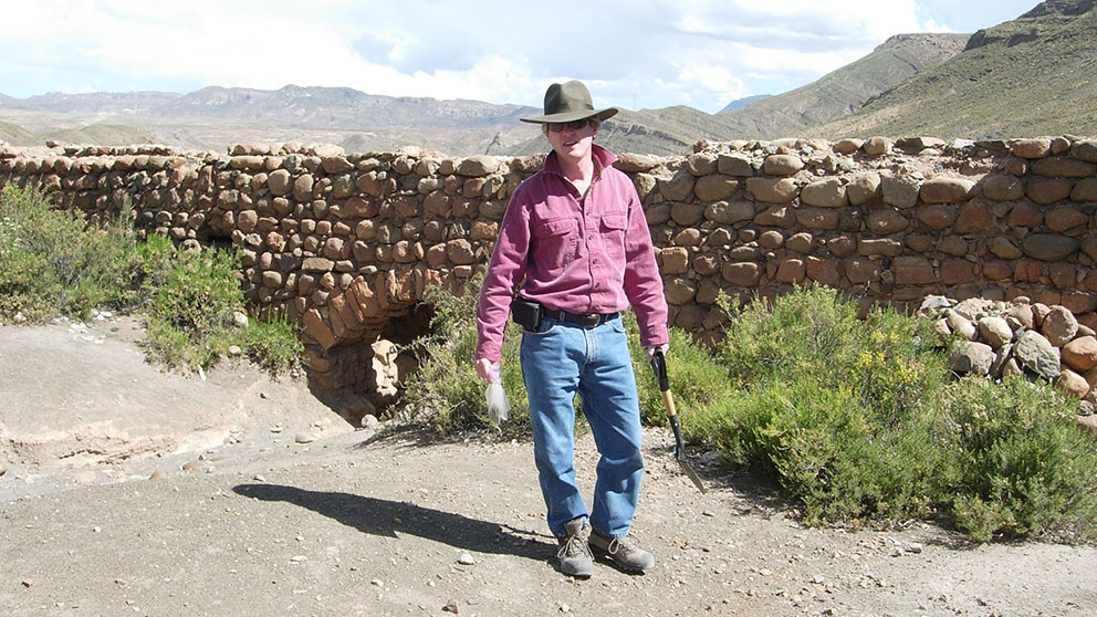 A man holds a shovel in front of a stone wall.