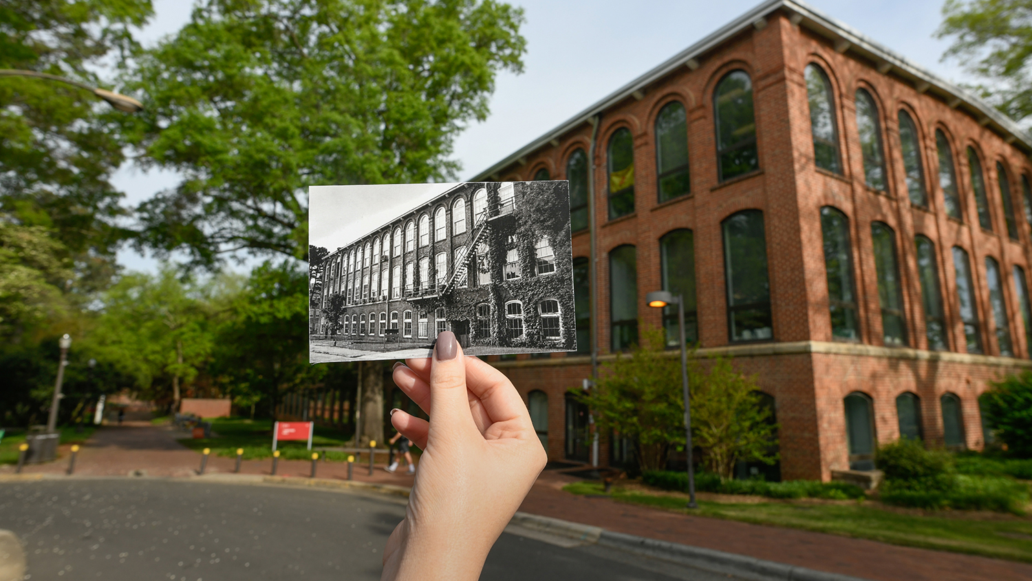A hand holds an old photo of NC State's Tompkins Hall, in front of the modern-day Tompkins Hall